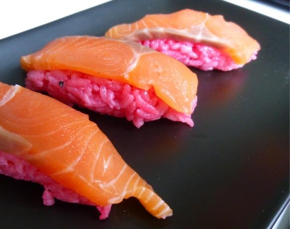 Die Kombination von rosafarbenem Reis und orangefarbenem Lachs ist skurril, aber geschmacklich unterscheidet sich der gefärbte Reis nicht vom ungefärbten.